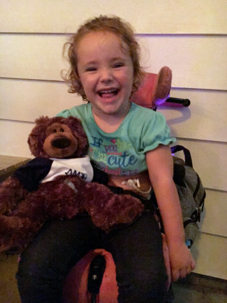 Young girl with feeding tube holding a stuffed bear with feeding tube